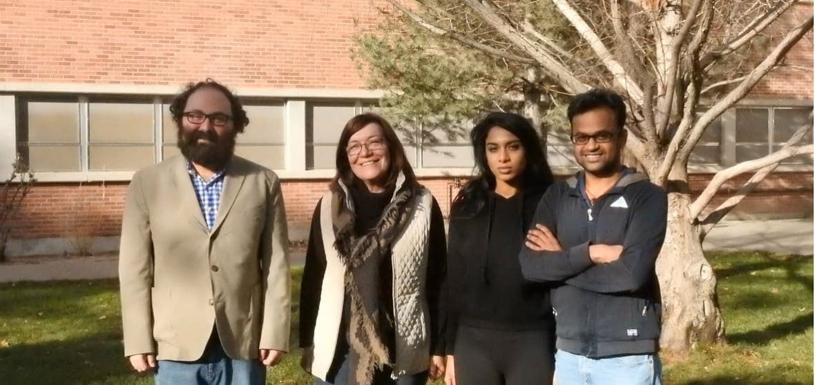 Two professors and two students stand infront of a tree.
