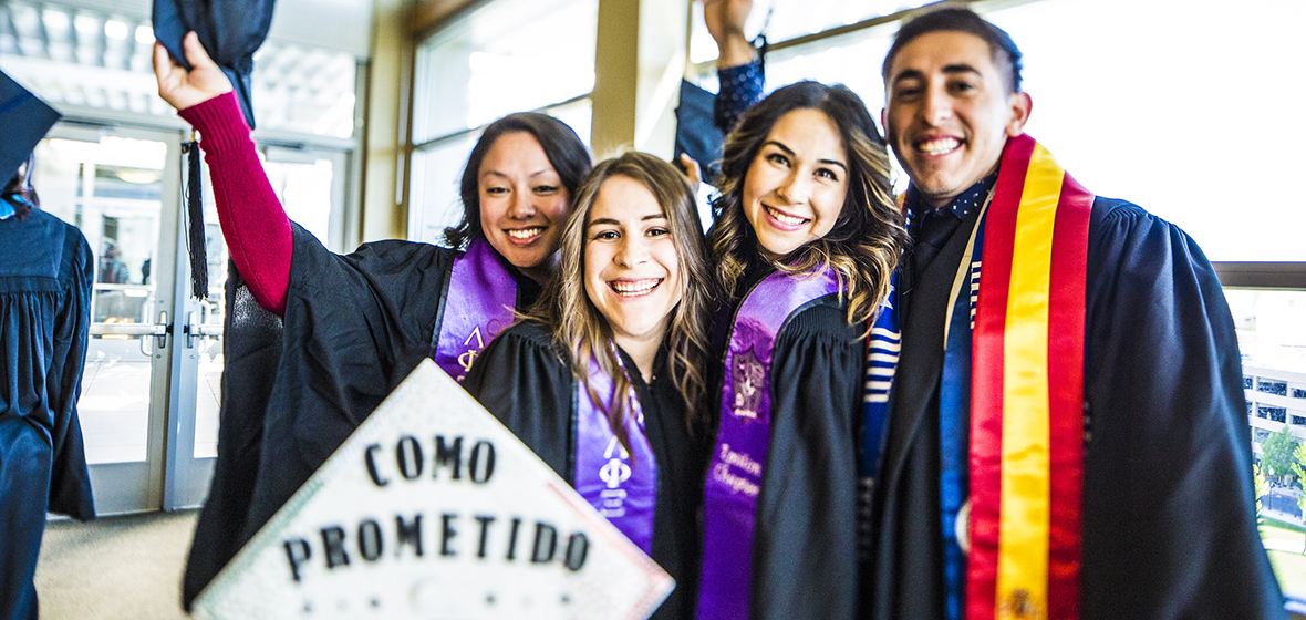 "Four students celebrate at Commencement. One student's graduation cap says, ""Como Prometido BSN"""