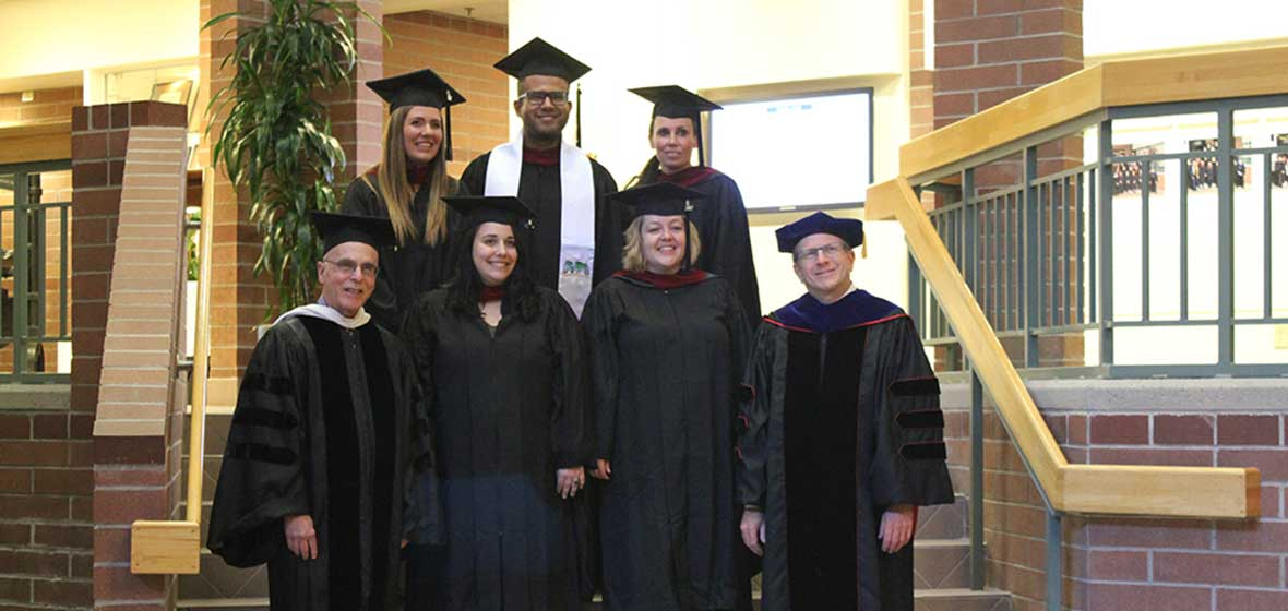 A group of people in graduation robes stand on a set of stairs.