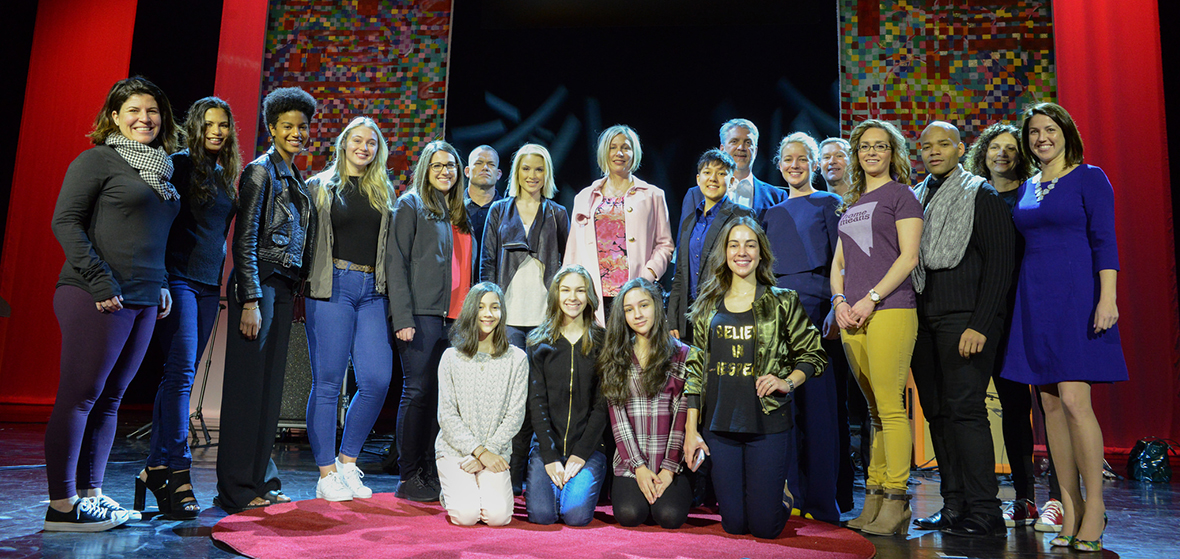 A group of people posing in front of a camera at TEDxUniversityOfNevada event, inside the Grand Sierra Grand Theatre.