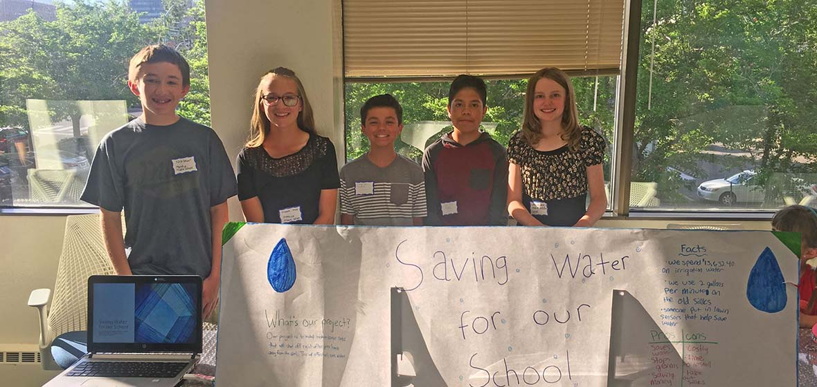 A group from Mendive Middle School stand at their energy proposal table