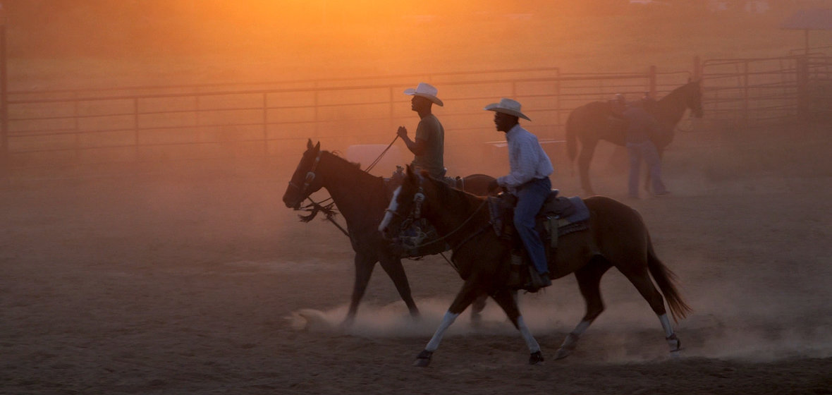 Spencer Nero and Darius Ford ride horses at sunset
