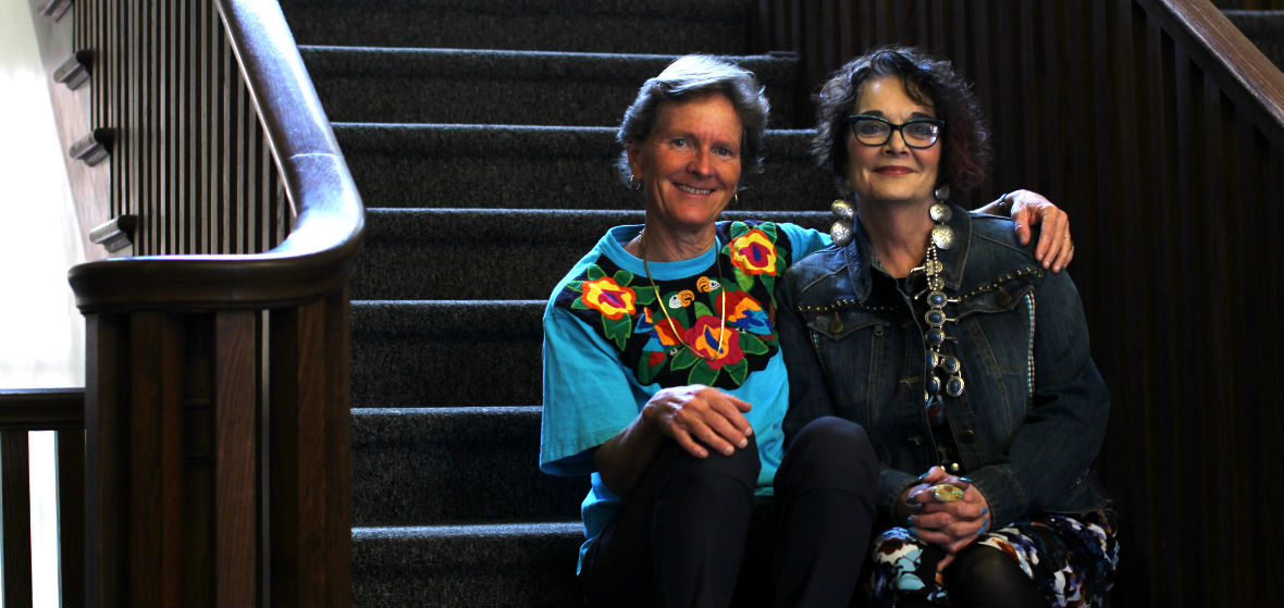 Cheryll Glotfelty and Gailmarie Pahmeier sit together on stairs