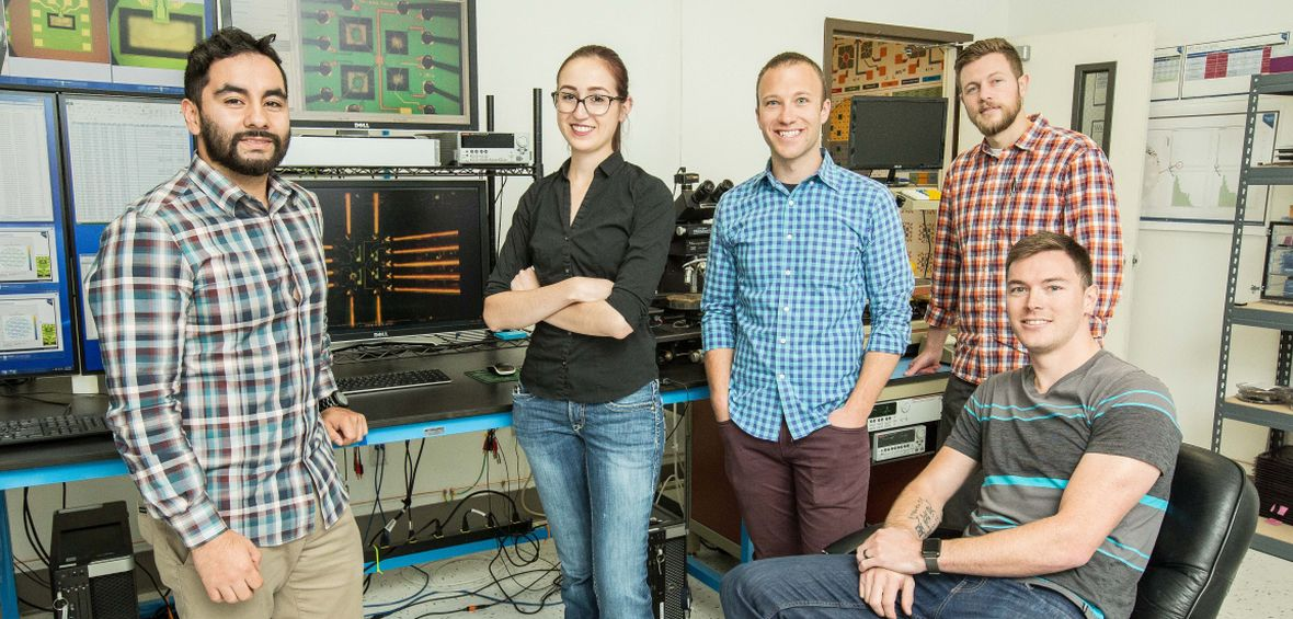 5 University alumni who work at NevadaNano are photographed in a laboratory setting.
