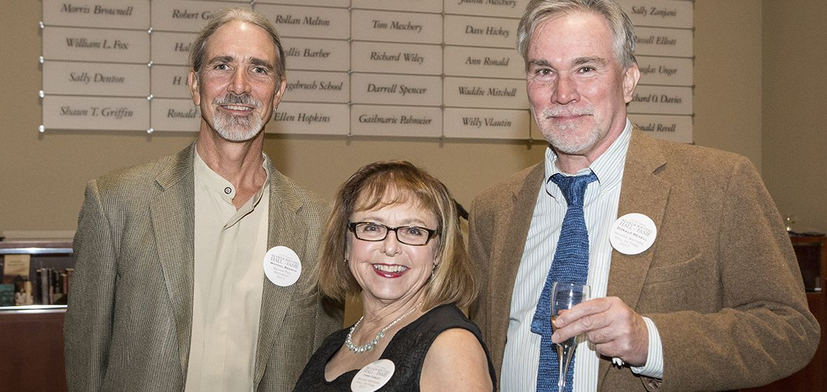 Silver Pen award winner Michael Branch stands in front of the wall of honor with Hall of Fame inductees Terri Farley and Donald Revell in the Leslie Harvey and Robert George Whittemore Tower Entry and Reception Gallery of the Mathewson-IGT Knowledge Center.