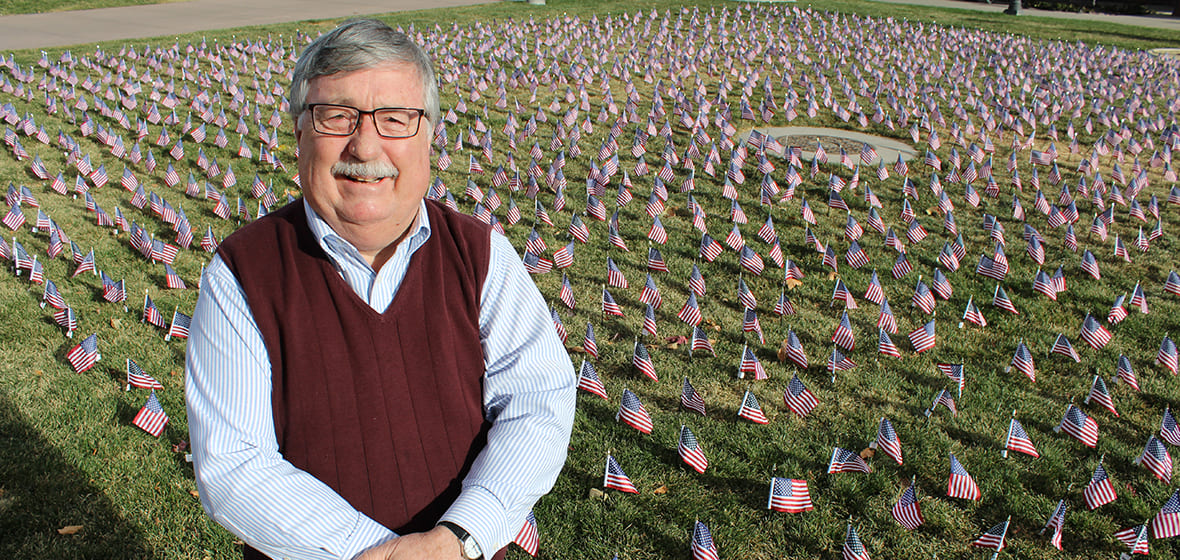 Professor Bob Felton poses in front of American flags decorating the lawn in front of the Joe Crowley Student Union.