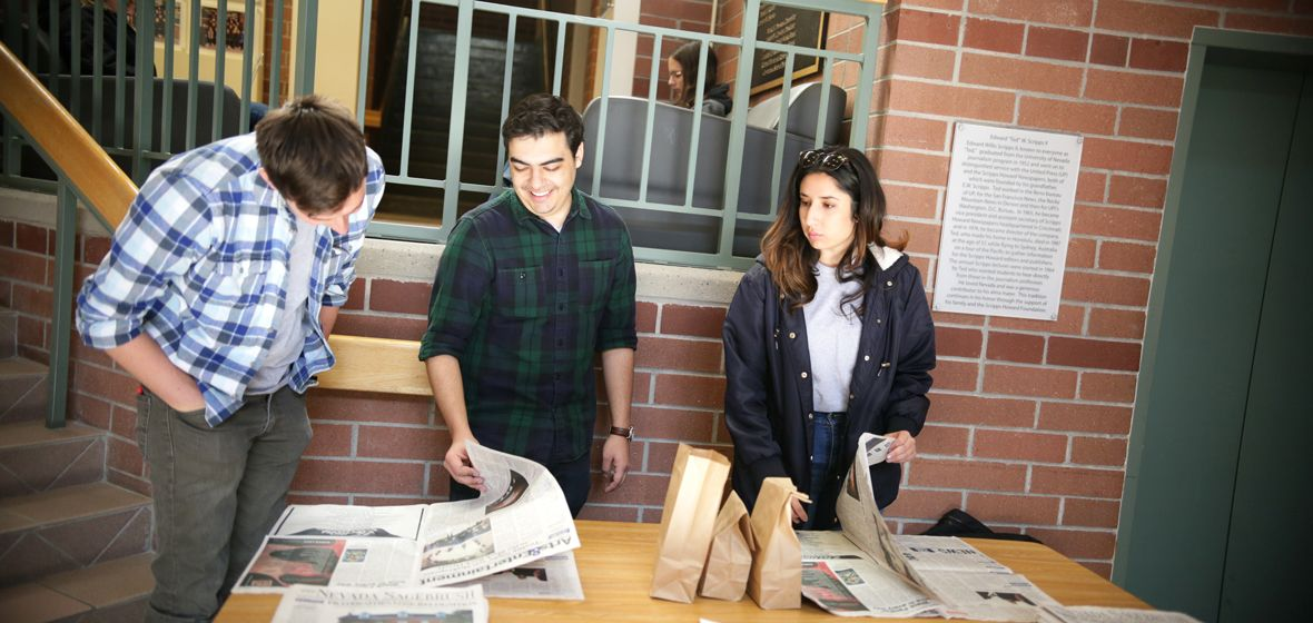 A group of students look at something on a table.