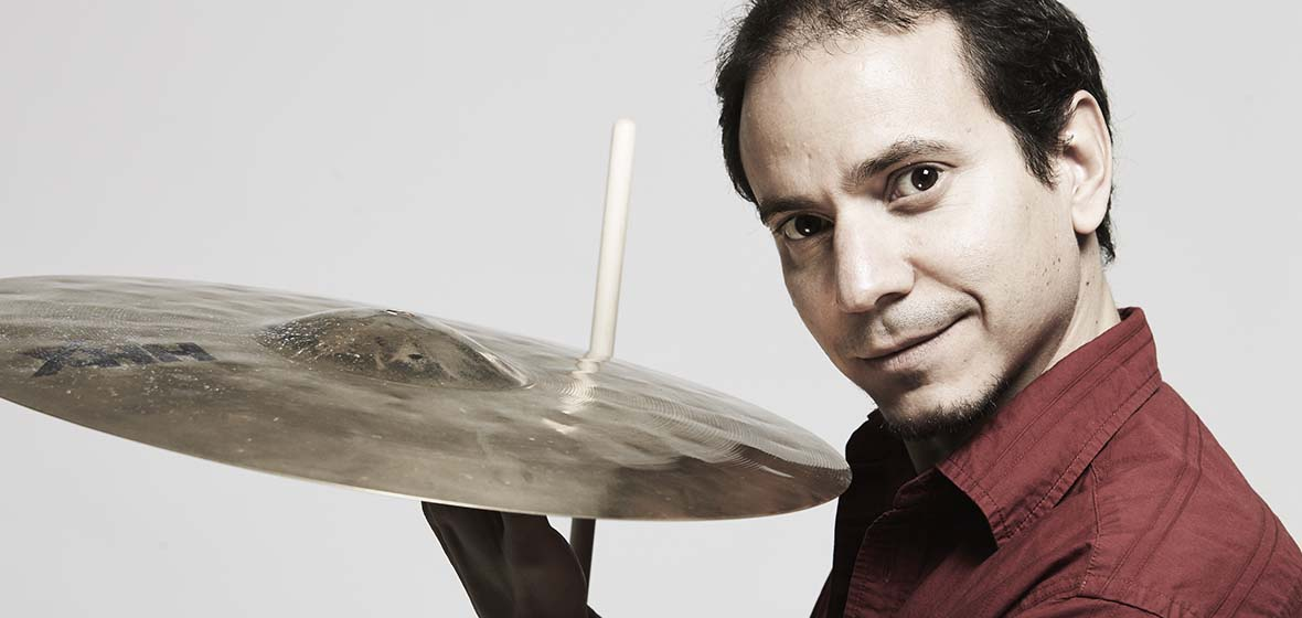 Dafnis Prieto poses with a cymbal in hand