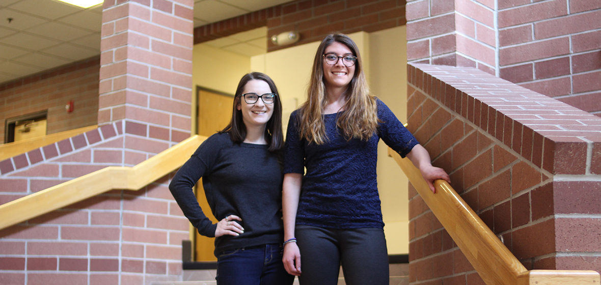 Madeline Purdue (left) and Andrea Heerdt (right) pose for a photo in the Reynolds School of Journalism's atrium.