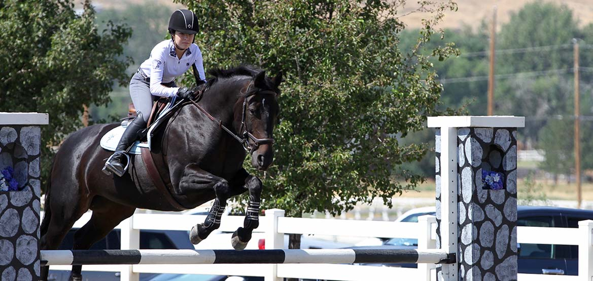 Girl riding a horse as the horse clear a jump