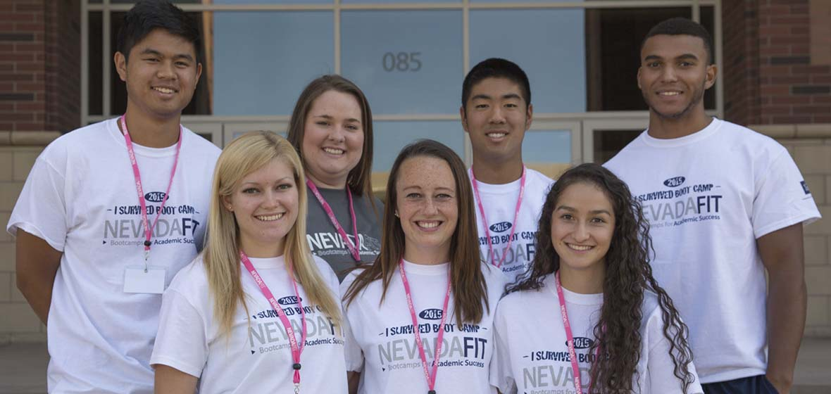 Seven students in white NevadaFIT T-shirst pose for a photo while gathered on the University of Nevada, Reno campus.