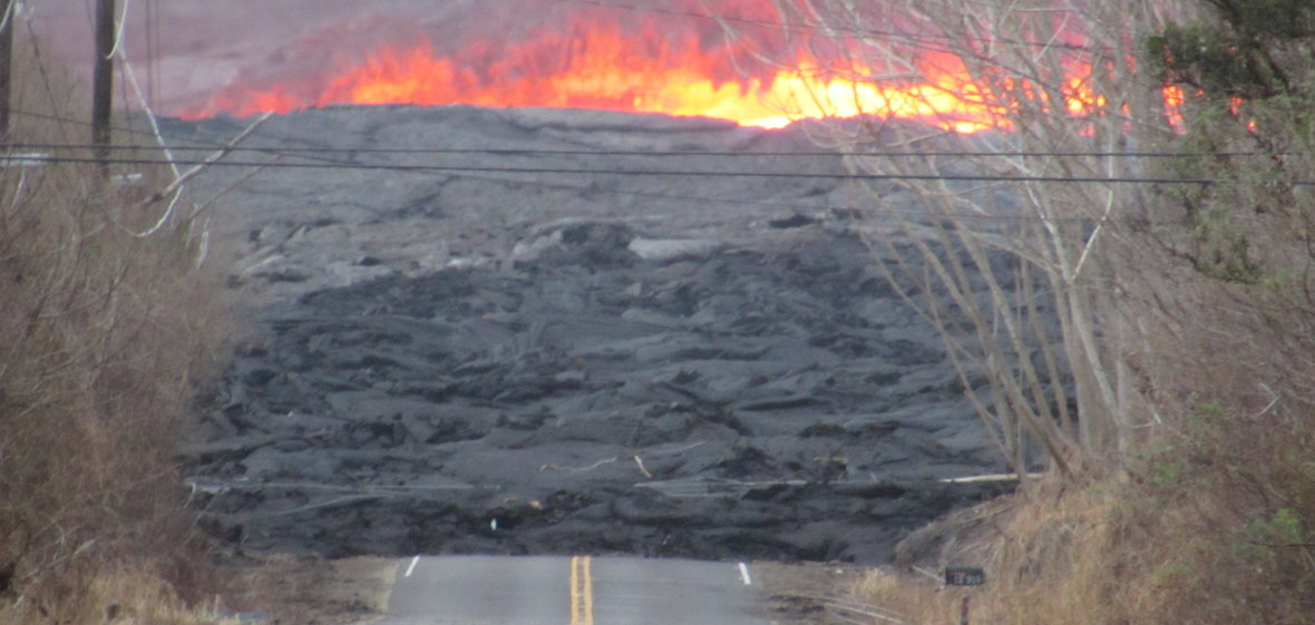 Lava flow in Kilauea swallows paved road with trees and a mailbox in the foreground and flames in the background