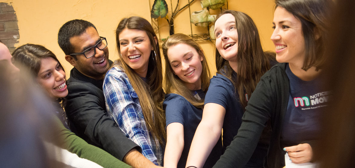 Five students and a professor place hands together in a circle indoors.