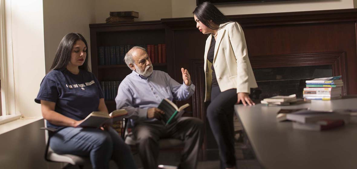 A professor, middle, sitting, instructing two students