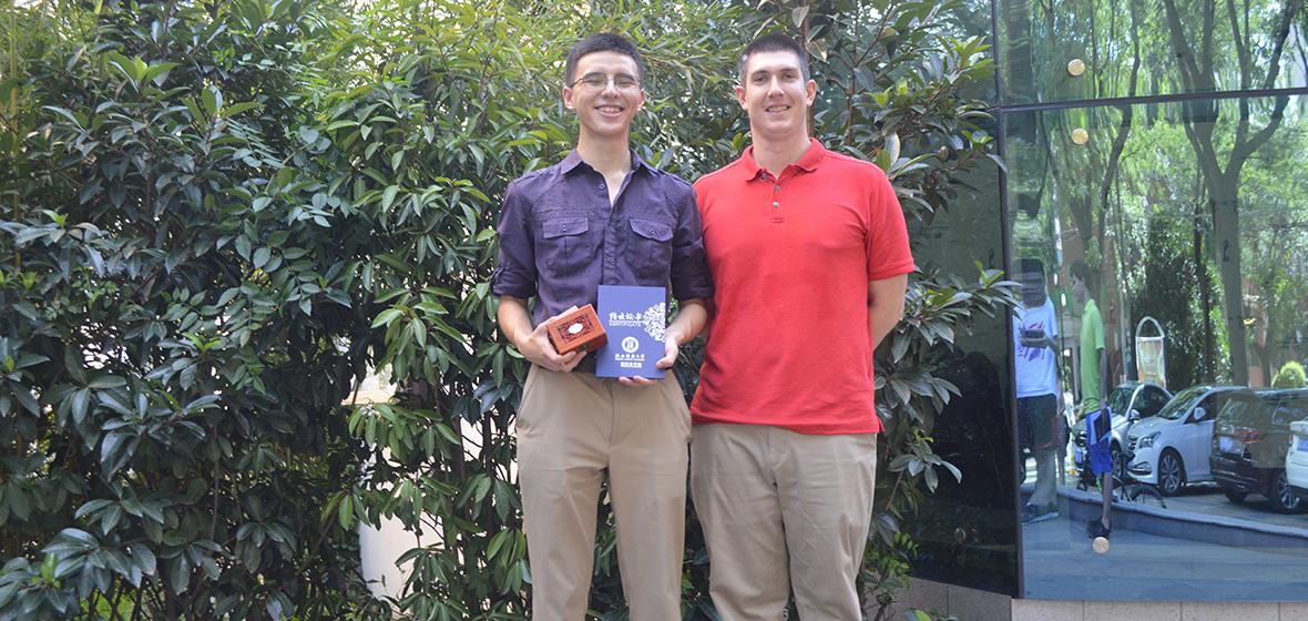Daniel Lang holds award next to fellow student
