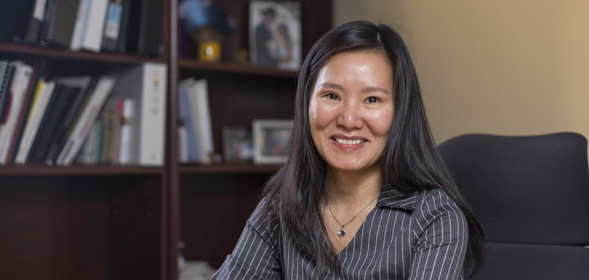 Dr. Yumei Feng sitting in her office with book shelves in the background