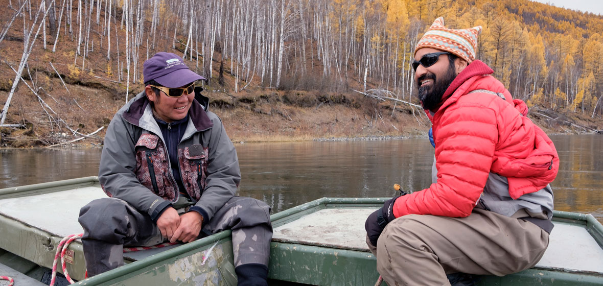 Ganzorig Batsaihan (left) sits with Sudeep Chandra on a river boat