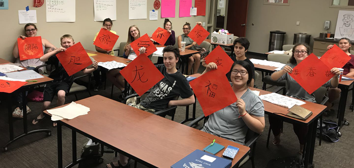 Students sit in classroom while holding up red papers with Chinese calligraphy