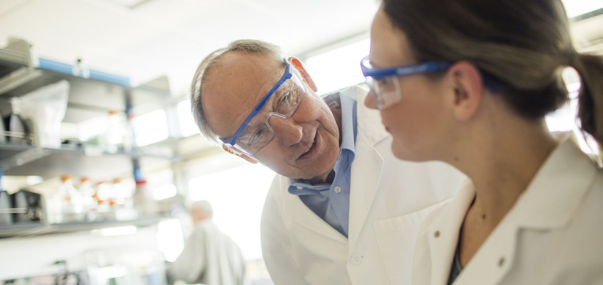 Professor Tom Kozel talks with a colleague in a laboratory.