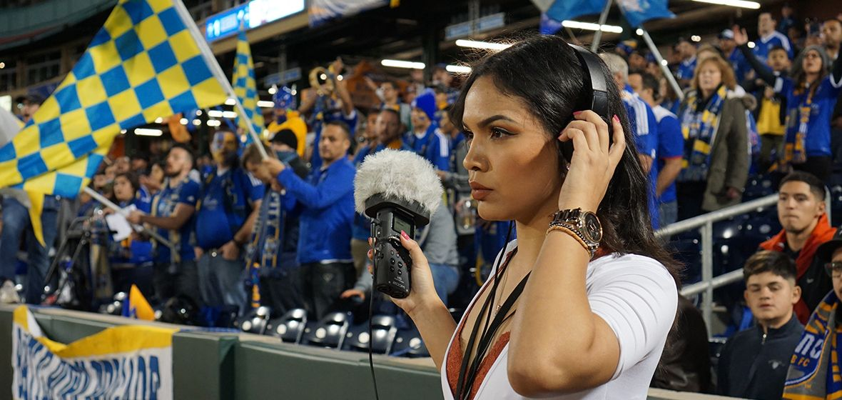 Woman stands with headphones and a microphone in front for a crowd of people.