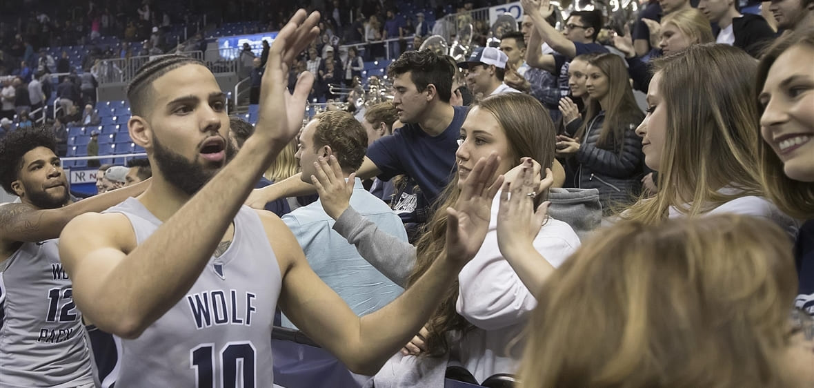 Caleb Martin high fives fans at Lawlor Events Center