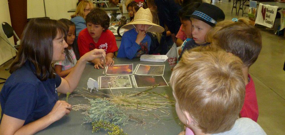 Presenter explaining vegetation photos and samples to five elementary students