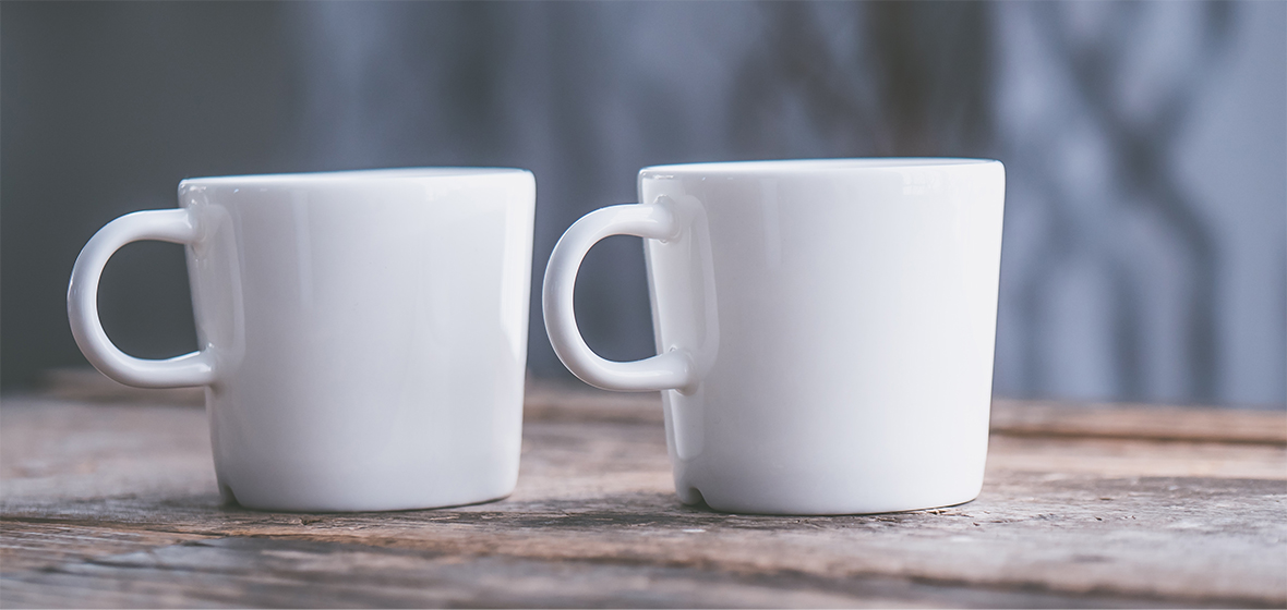 Two coffee mugs on a wooden table