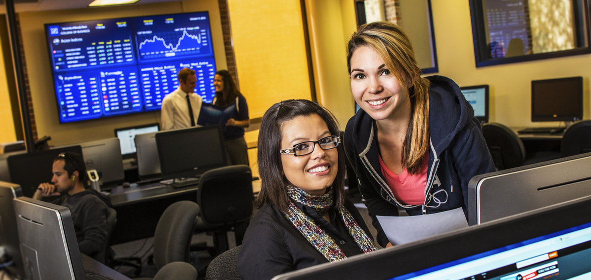 Business students in a computer lab with financial data in the background