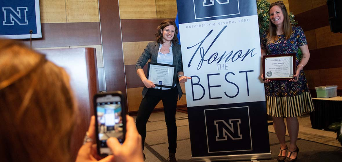 Two University of Nevada, Reno faculty members pose next to an Honor the Best banner while someone takes a picture of them with a cell phone