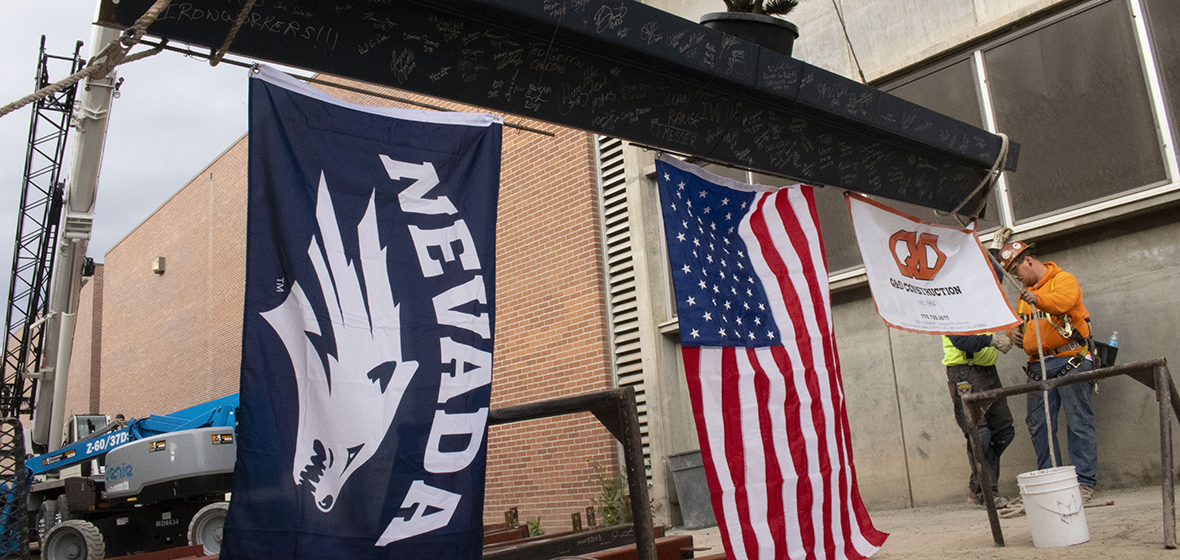The flags of the Nevada Wolf Pack, United States of America and Q&D Construction hang from a steel beam.