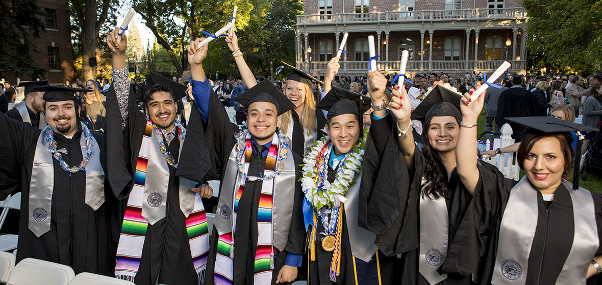Graduates hold up their diplomas in front of Morill Hall