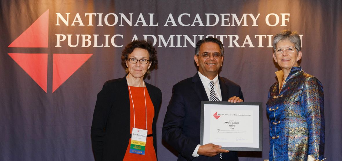 Two National Academy of Public Administration representatives present Mridul Gautam with a framed recognition of his induction.
