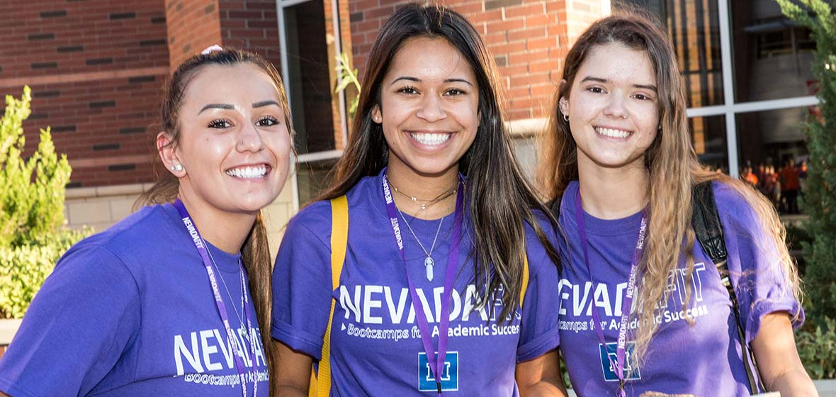 Three freshmen in purple NevadaFIT T-shirts pose for a photo.
