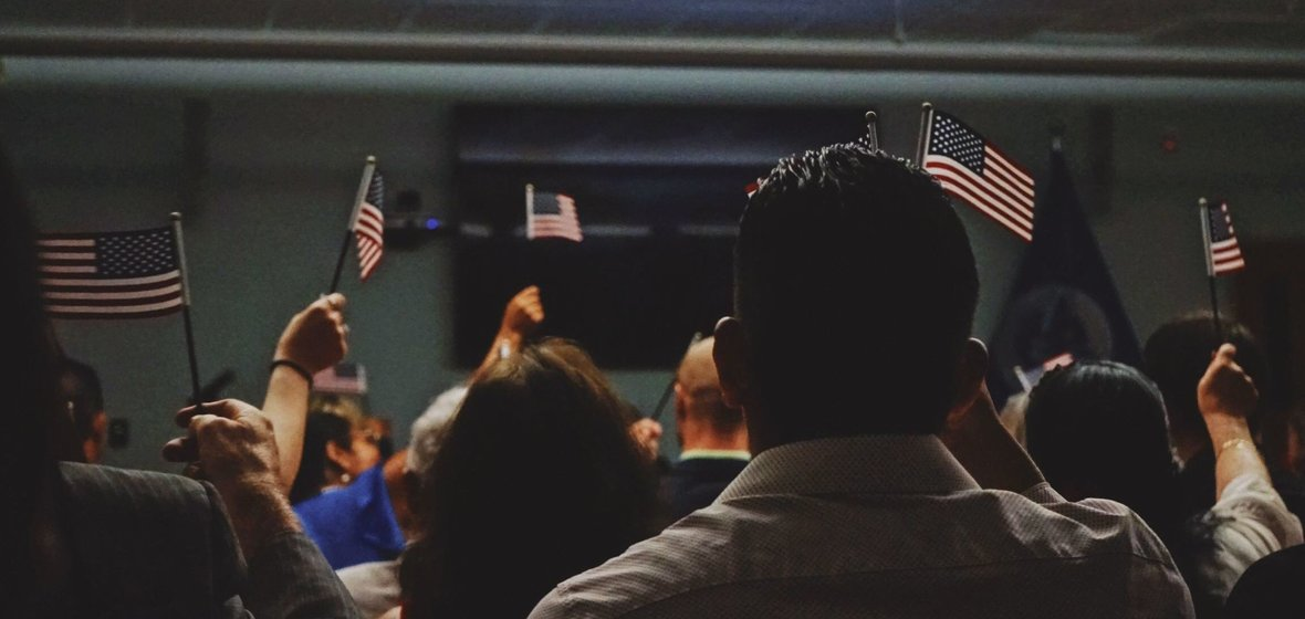 A group of people in a classroom holding up small American flags