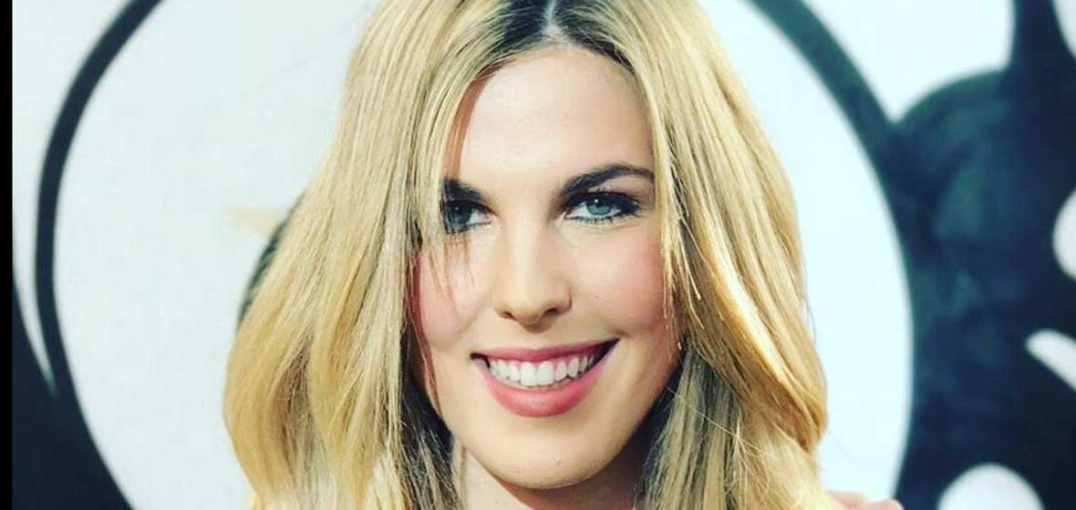 A blonde woman smiles for the camera.