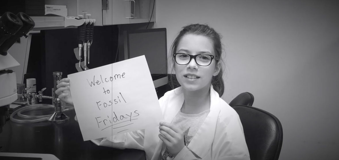 """Girl holding sign that reads """"Welcome to Fossil Fridays"""""""