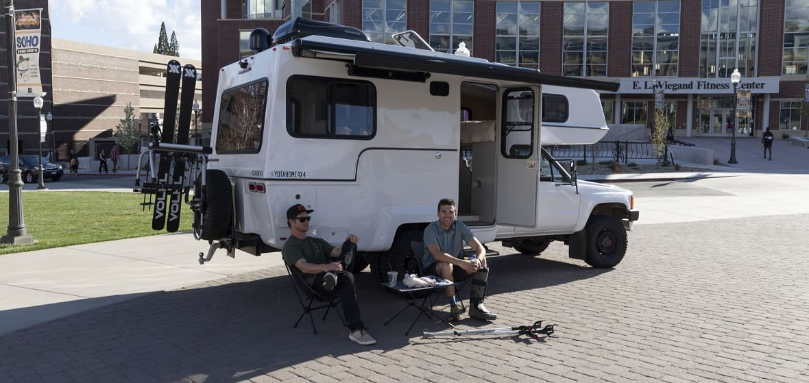 Two students sit in front of a Sturn Designs concept vehicle outside of the Joe Crowley Student Union.