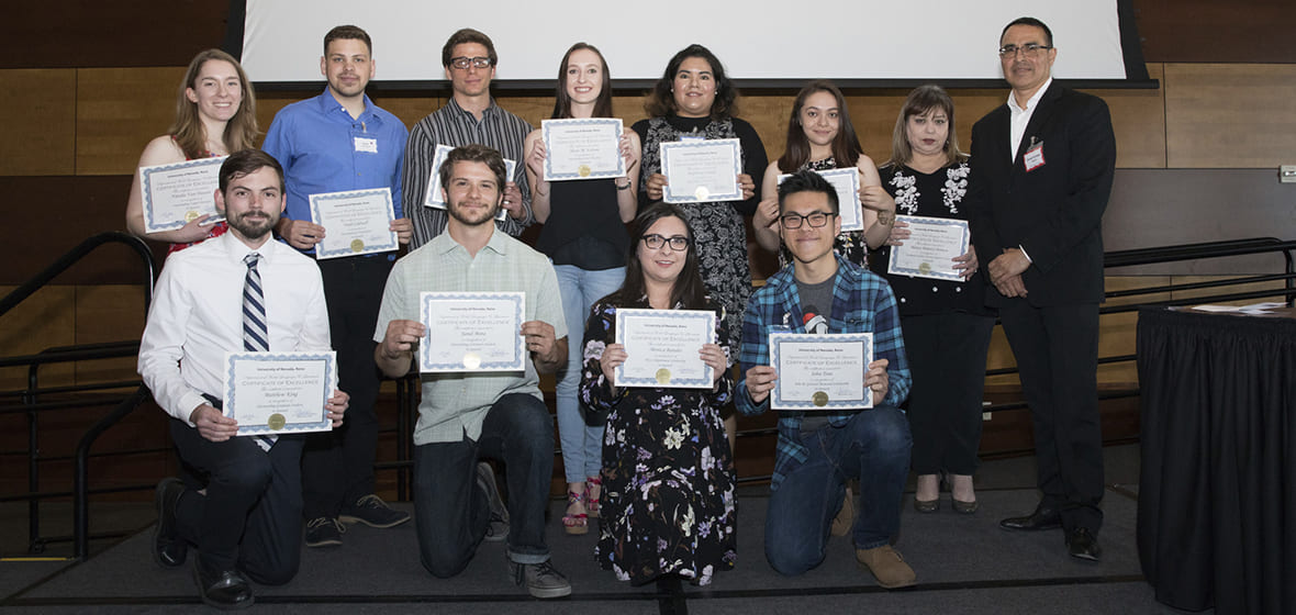 Award winners hold up certificates on stage during 2018 awards ceremony.