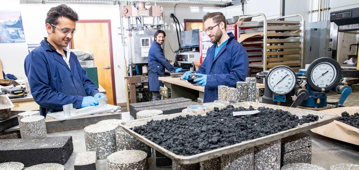 Three men working in a pavement lab.