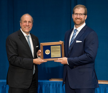 Rick Kraus stands with Undersecretary of Science at the Department of Energy, Paul Dabbar to accept his award.
