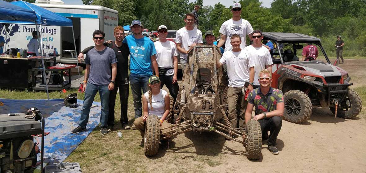 A group of students around a muddy racing car.