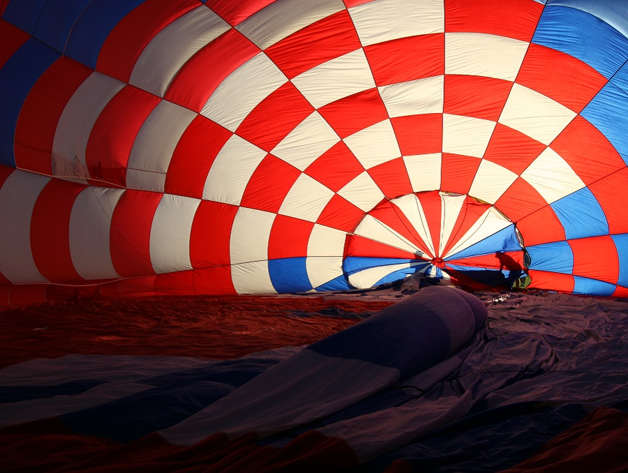 Deflated hot air balloon with red and white checkers and people's shadows in the background.
