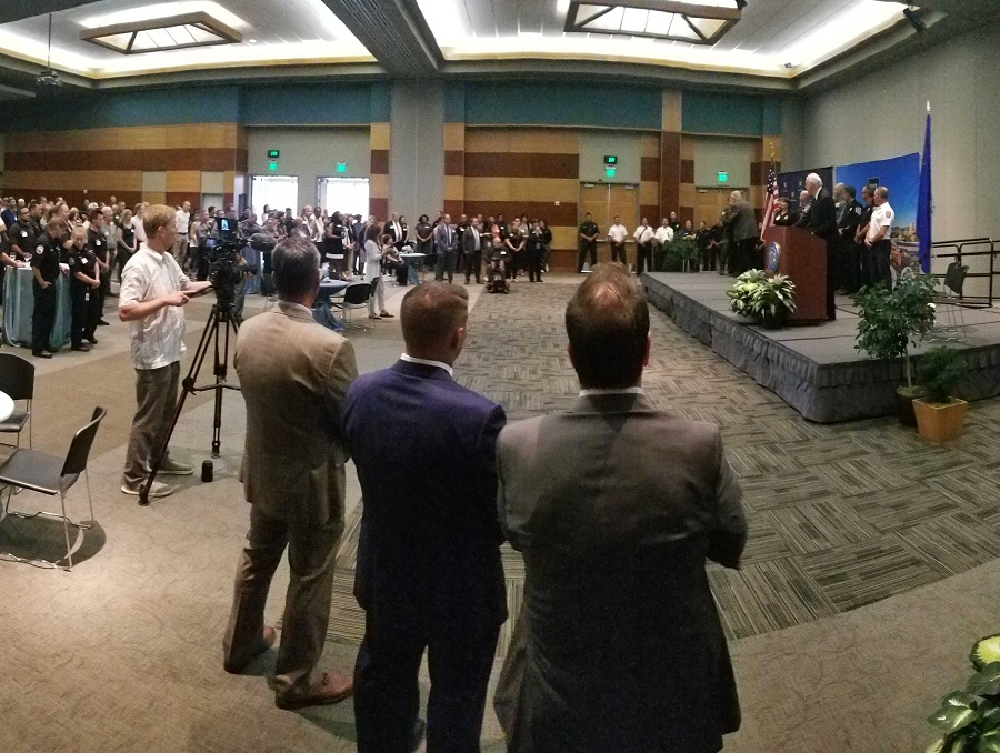 A room filled with people sitting and standing while listening to President Marc Johnson, who is at the podium