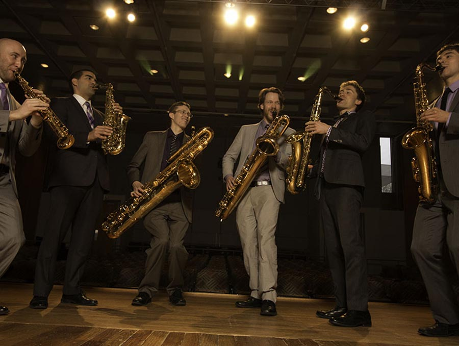 A group of musicians in suits gathered playing a variety of different saxophones