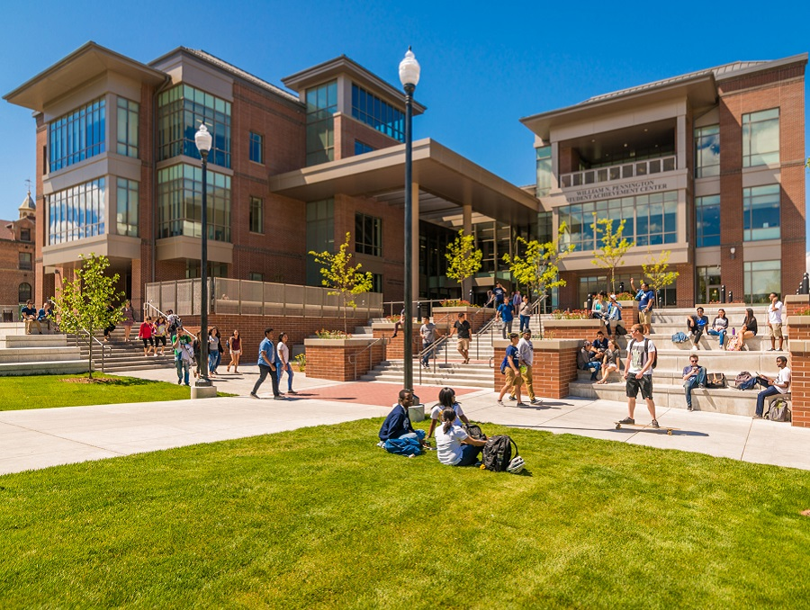 Pennington Student Achievement Center during a typical sunny day with students walking by and sitting on the lawn and various benches