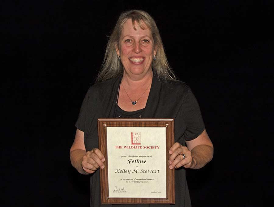 Kelley Stewart holding up award certificate