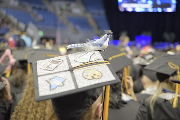 A 2019 Winter Commencement graduate with a mortar board that has a bird sitting on it with its own mortar board