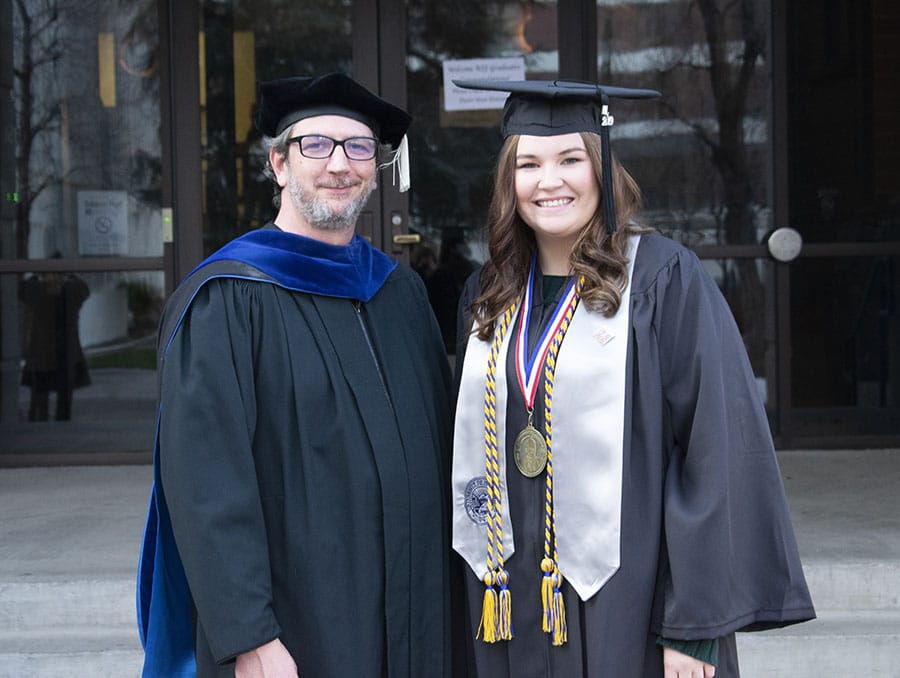 A faculty member and student pose in front of the Reynolds School of Journalism