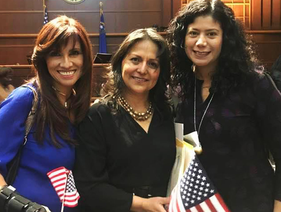 Lizeth Ramirez-Barroeta in a courtroom holding a U.S. flag and flanked by two of her coworkers.