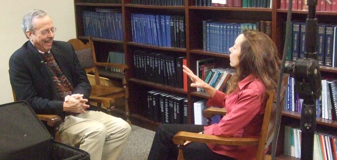 George Lewis and Valerie Fridland sitting and talking in a room with books and bookshelves behind them.
